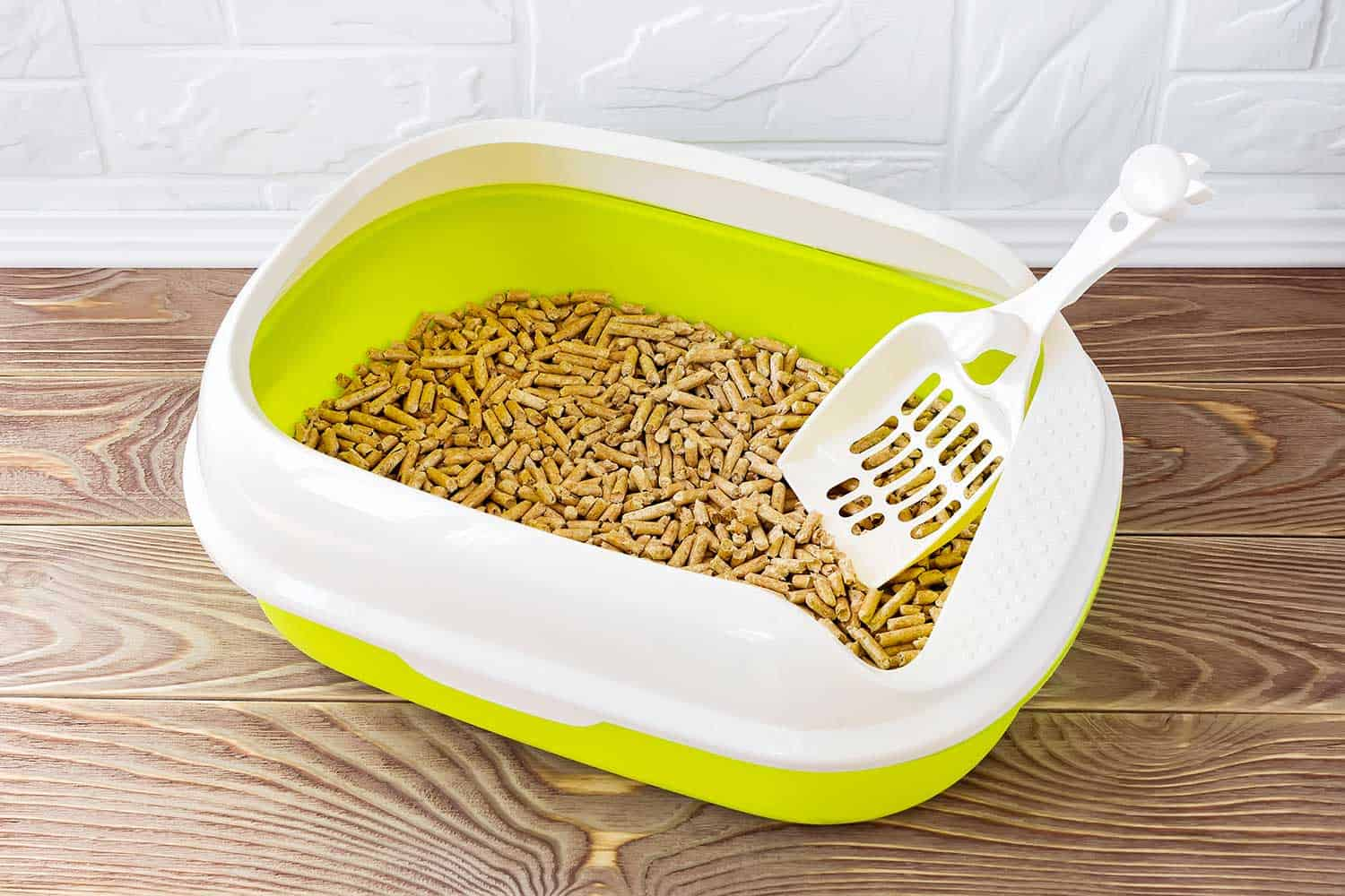 High sided cat litter tray with wooden pellets and scoop on a brown wooden floor